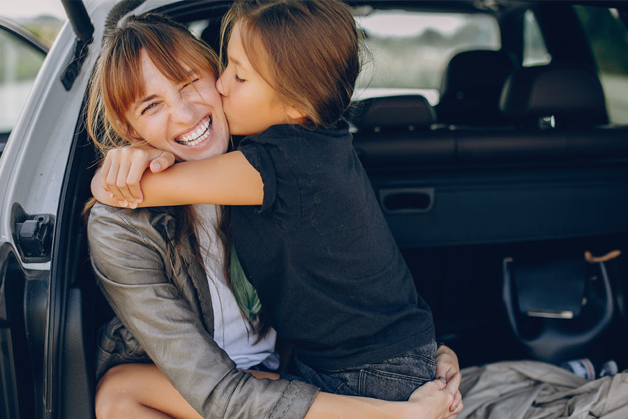 Personal Insurance - Mother and Daughter Hugging in the Car